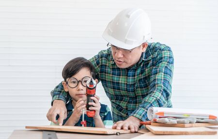 Father is safely teaching his son to use the screwdriver to work the wood.