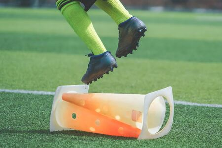 Foto de Child feet with football boot is practicing Jumping over the cone on soccer field, For children Soccer academy training concept. - Imagen libre de derechos