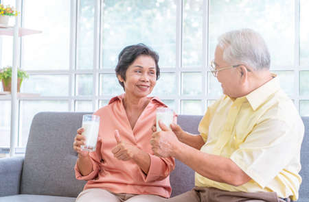 Photo pour Two senior couple is drinking milk while relaxing on a sofa living room for retiredment wellness and healthy lifestyle concept. - image libre de droit
