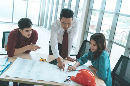Photo pour Construction Boss with business man engineer and architect is discussing on working table with building plan - image libre de droit