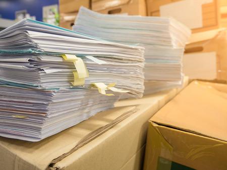 Foto de Stacks of document paper and files folder in front of cardboard boxes background, Concept work hard, Lot of work. - Imagen libre de derechos