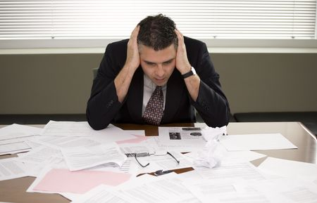 Foto de A businessman pondering over the paperwork - Imagen libre de derechos