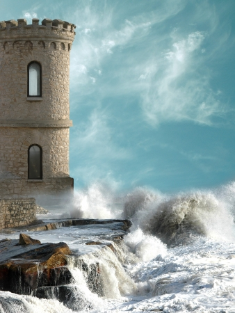 Medieval tower with agitated coast and big rocks
