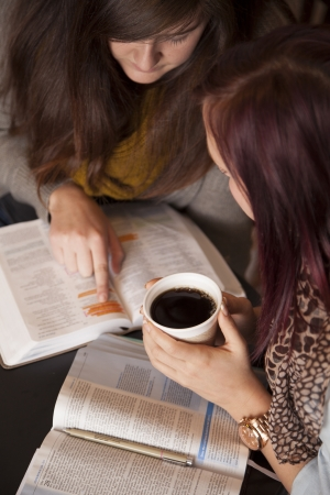 Two young women study the bible together while drinking coffee.