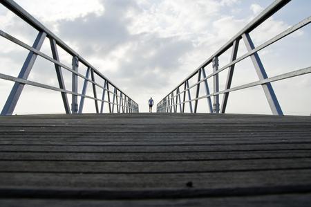 man walking away on a bridge