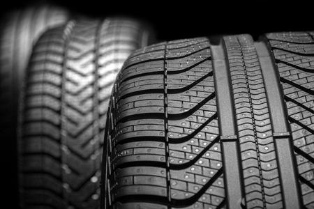 Photo pour Row of car tires with a profile close-up on a black background. - image libre de droit