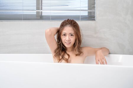 Photo pour Portrait of young attractive asian girl takes a bath with candles relax in the bathroom. Beauty woman in spa treatments. Healthy perfect glow skin care concept - image libre de droit