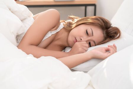 Photo pour Portrait of beautiful Asian woman with attractive smile enjoy fresh soft bedding linen mattress in white bed room modern apartment. Cute asia girl sleep resting, good night sleep concept. - image libre de droit