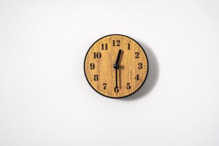 Foto de wood office wall clock with white dial on white background. wall clock on white background, top view. - Imagen libre de derechos