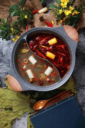 Photo for Spicy red oil and clean soup hotpot in a ceramic pot - Royalty Free Image