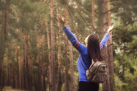 Photo pour Hiker woman with raised arms up on nature outdoors, back view - image libre de droit