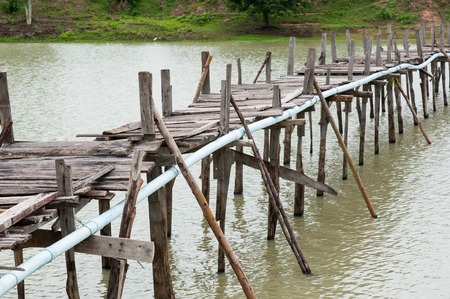 Old wooden  long  bridge cross the lake.