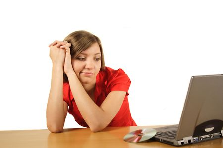 A young handsome woman waiting for the installation process of her notebook computer. All isolated on white background.