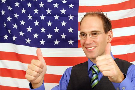 A young businessman jubilation in front of the flag of the United States of America.