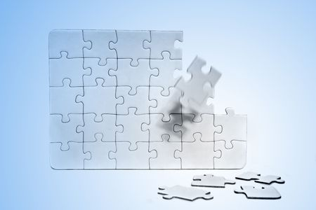 A jigsaw puzzle with various missing pieces. All in front of light blue background.