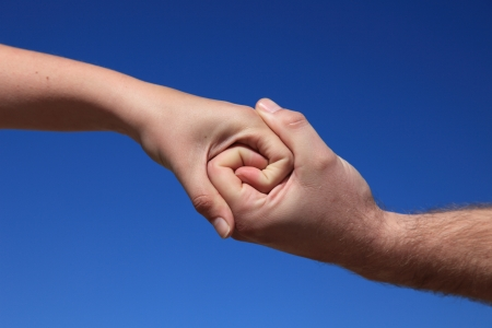 Two persons holding hands in front of bright blue sky