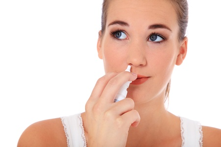 Attractive young woman using nasal spray. All on white background.