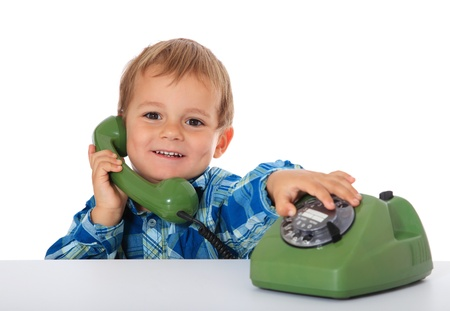 Cute caucasian boy using telephone. All on white background.