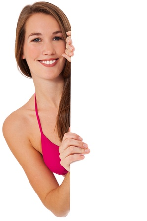 Attractive woman in bikini standing behind white wall. Isolated on white background.