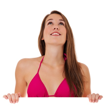 Attractive woman in bikini standing behind white wall, looking up. Isolated on white background.