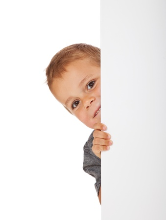 Cute little boy hiding behind a white wall  All isolated on white background