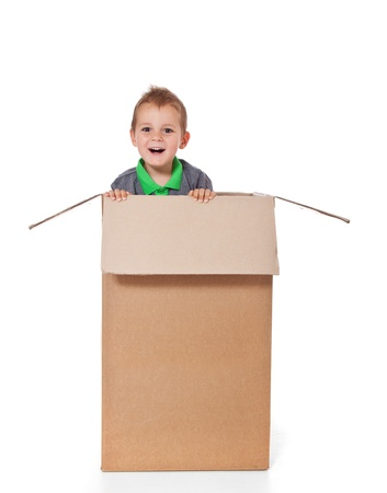 Cute little boy sitting in a box  All isolated on white background