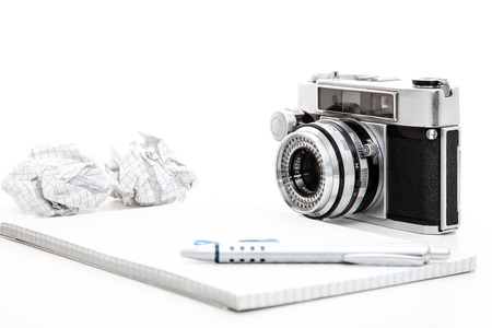 Notepad, pen and retro camera. All on white background