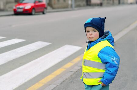 Photo pour Child in front of pedestrian crossing. A little boy finds out if he can cross the crossswalk. He wears reflective vest because of safety. Car in the background. Child concept. Traffic concept. - image libre de droit