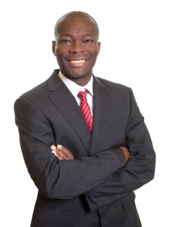African businessman with crossed arms laughing at camera