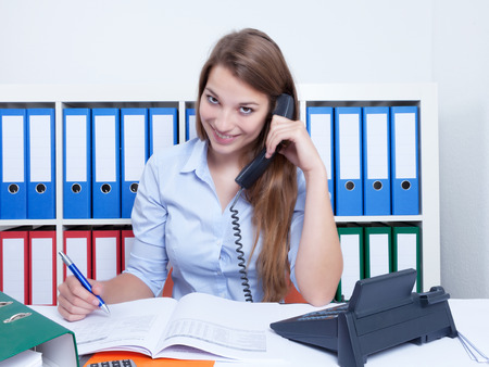 Attractive woman with long blond hair at office talking at phone