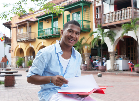 Happy latin student in a colonial town with paperwork