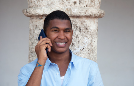Attractive latin guy with phone in a colonial town