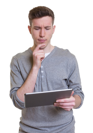 Thinking guy in a grey shirt working with tablet computer
