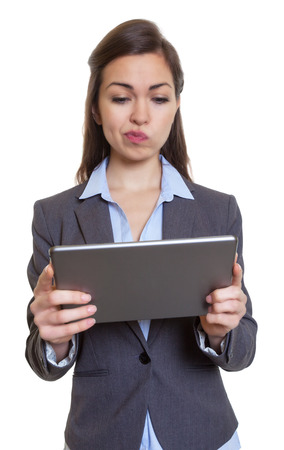 Thinking businesswoman with brown hair and tablet computer