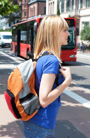 Blonde female student waiting for the bus