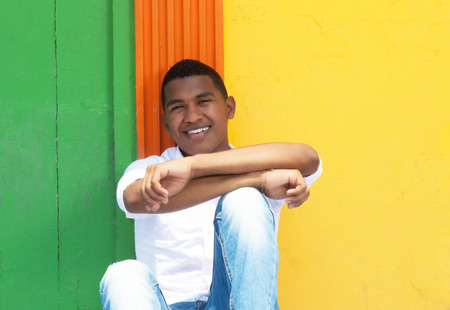 Laughing caribbean guy sitting in front of a colorful wall