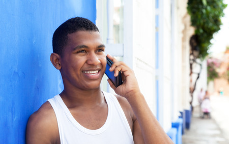 Latin guy talking at phone in front of a blue wall