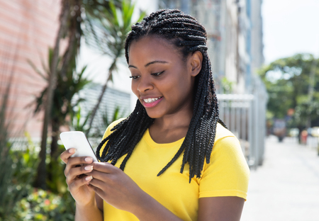Photo pour African american woman in a yellow shirt texting message with mobile phone - image libre de droit