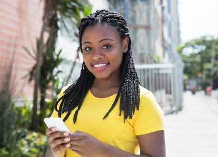 Photo for African american woman in a yellow shirt typing message with mobile phone - Royalty Free Image
