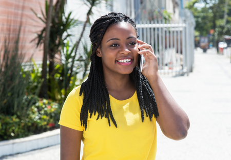 Photo pour Happy african american woman in a yellow shirt at mobile phone - image libre de droit