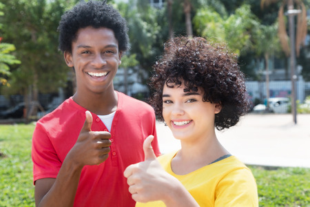 Caucasian girl with african american boyfriend showing thumbの写真素材