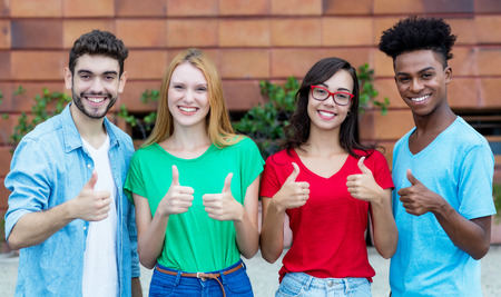 Photo pour Group of four young adults of generation y showing thumbs - image libre de droit