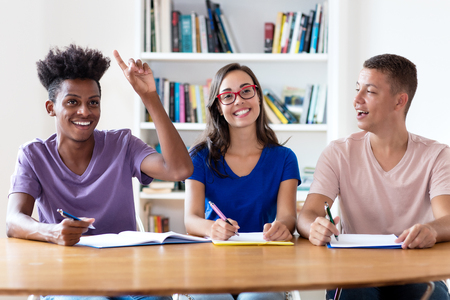 Photo pour African american male student raising hand in classroom of school - image libre de droit