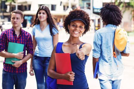 Photo pour Laughing african american young adult woman with students in city - image libre de droit