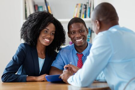 Photo pour Real estate agent offers new house for african american couple - image libre de droit