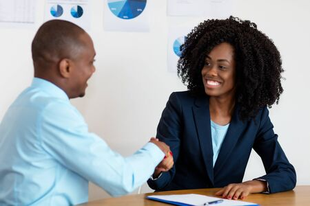 Photo pour Handshake of african american businesswoman with businessman after job interview - image libre de droit