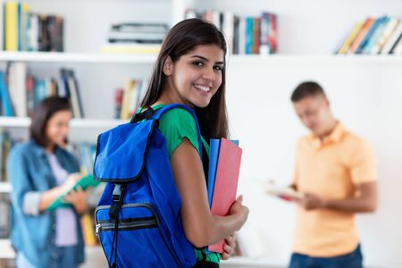 Foto de Pretty hispanic female student with group of young adults - Imagen libre de derechos