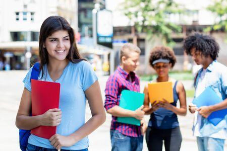 Photo pour Young hispanic female student with group of multi ethnic young adults - image libre de droit