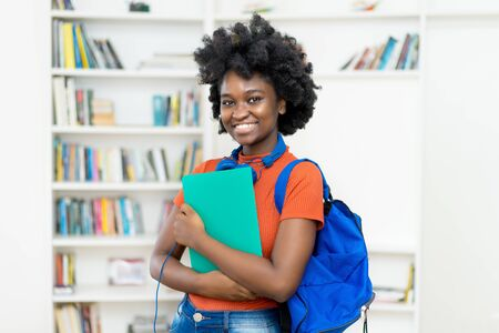 Foto de Beautiful afro american female college student with backpack and paperwork - Imagen libre de derechos