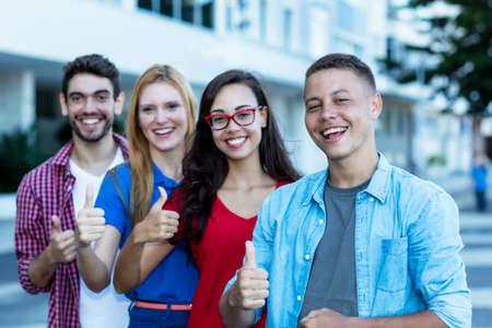 Foto de German young adult man with international friends in line showing thumb up - Imagen libre de derechos